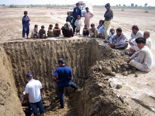 Researchers unwisely inspecting an unsupported excavation. On no account should anyone, ever do this, whether they are wearing hard hats or not.