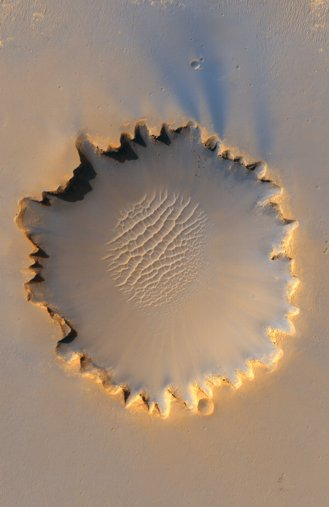 The 800m diameter Victoria crater showing the unusual scalloped walls, and sief dunes on the floor. Photo by NASA. Image taken 3 October 2006 by the High Resolution Imaging Science Experiment (HiRISE).