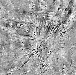 Tyrrhenia Patera on Mars (~200 km diameter). This is a flatter cone than Ceraunius and Uranius Tholus, but is thought to be composed of horizontally bedded ash deposits. The caldera and a flat-floored troughs merge into one another (MOC WA).