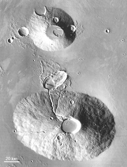 Ceraunius Tholus (bottom ) and Uranius Tholus (top) on Mars (~130 and ~60 km diameter). The radial and later sinuous channels suggest that the material was easily erodable, ash rather than lavas, and the steep conical piles support this (THEMIS).