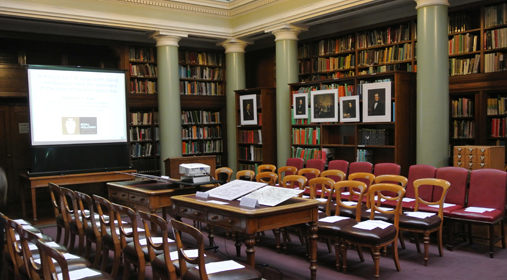 The Upper Library arranged with seating arranged in Parliamentary Style and reproduction paintings from the period on the bookshelves
